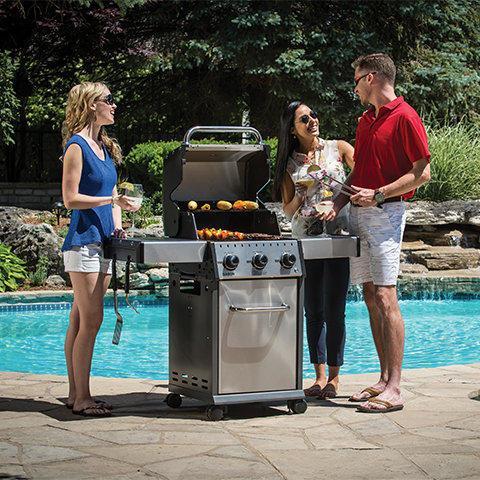 People grilling with a Broil King grill by the pool